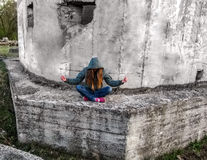 A girl with long blond hair in a hood sits in a lotus pose. She sits outdoors on a concrete wall and tilted her head down Royalty Free Stock Photos