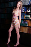 Girl with long blond hair in short dress standing. Next to shelves of books and looking at camera stock photo