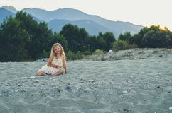 Girl with long blond hair sitting alone  by the sea Royalty Free Stock Photos