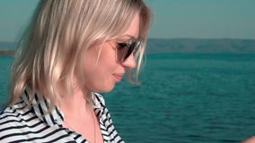 Girl with long blond hair walking along the shore, smiling and feeling happy and free stock video footage
