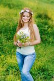 Girl with long blonde hair is looking at bouquet royalty free stock photography