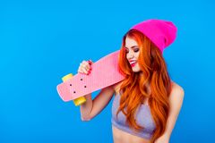 Girl with long board. More colors to your life! Foxy cute charmi. Ng model in hat and with skate board on blue background. Ginger is so attractive and colorful Royalty Free Stock Photography