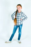 Girl with long braid in a plaid shirt and jeans Stock Photography