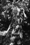 Art black and white photography. Unusual appearance. Girl with long braids in a floral dress against the background of a large bush of roses. Woman posing in the Royalty Free Stock Photo