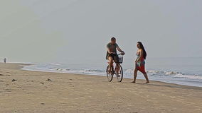 Girl in long bright dress catches man on bicycle on beach stock video