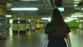 The girl with long brown hair goes on the underground parking. Lamps on the underground parking. The girl goes on the. On the video you can see as the girl with stock footage