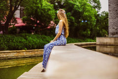 Girl with long brown hair sits near water turned her back to the camera in the Park Stock Photography
