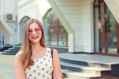 Girl with long brunette hair in pink heart-shaped sunglasses laughing outdoors stock images
