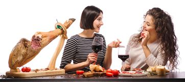 Ladies speak, joke and smile at the kitchen with wine and jamon. Isolated. A girl with long and curly hair bites a sandwich with meat while the second girl with Stock Photos