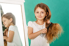 Girl with long curly hair and hairbrush Royalty Free Stock Photos