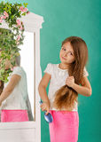 Girl with long curly hair and hairbrush Stock Photography