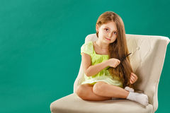 Girl with long curly hair and hairbrush Royalty Free Stock Photography