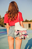 Girl with long dark hair is back with roller skates on her shoulder. Warm summer evening in the skate park. Outdoor stock image