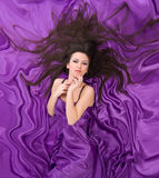 Girl with long dark hair of purple silk Royalty Free Stock Photo