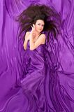 Girl with long dark hair of purple silk Royalty Free Stock Image