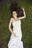 A girl with long dark hair wearing lying on grass Royalty Free Stock Photos