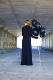 Girl in a long dress with black balloons Royalty Free Stock Photography