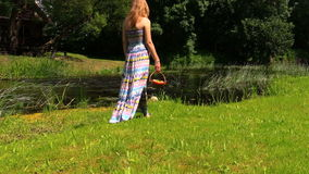 Girl with long dress go along river in hand basket of fruit stock footage