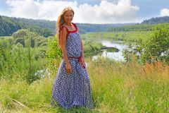 Girl in long dress with long hair smiling in nature stock photography