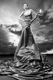 Girl in a long dress holds an exotic flower Royalty Free Stock Images