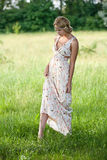 Girl in a a long dress on nature. Beautiful young girl in a bright dress on the nature of the long summer Stock Photo