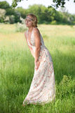 Girl in a a long dress on nature. Beautiful young girl in a bright dress on the nature of the long summer Stock Photos