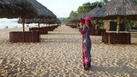 Girl in long dress poses on beach among sun umbrellas. Long-haired girl in long coloured dress and red hat poses on beach among reed sun umbrellas and goes away stock footage
