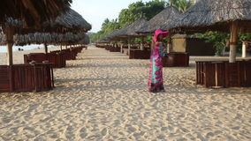 Girl in long dress poses on beach among sun umbrellas. Long-haired girl in long coloured dress and red hat poses on beach among reed sun umbrellas and goes away stock video footage