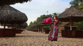 Girl in long dress poses on beach at umbrellas and comes. Long-haired girl in long coloured dress and red hat poses on beach among sun umbrellas and comes back stock video