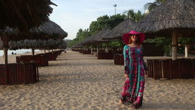 Girl in long dress poses on beach at umbrellas and comes. Long-haired girl in long coloured dress and red hat poses on beach among sun umbrellas and comes back stock footage