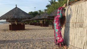 Girl in long dress and red hat poses by beach bamboo tower. Long-haired blonde girl in long coloured dress and red hat poses on beach by bamboo tower against stock video