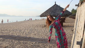 Girl in long dress and red hat poses by beach bamboo tower. Long-haired blonde girl in long coloured dress and red hat poses on beach by bamboo tower against stock video footage