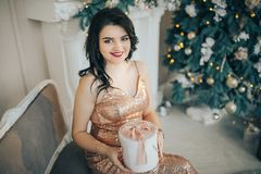 Girl in a long dress sitting near a Christmas tree and unpacking a gift. A brunette girl in a beautiful long dress sitting in a room near a Christmas tree and Stock Photos