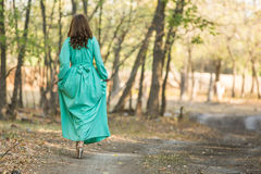 A girl in a long dress walking on a forest road Royalty Free Stock Photos