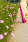 Girl with long dress walks in the flower garden stock photo