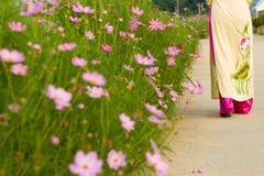 Girl with long dress walks in the flower garden stock images