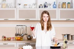 Girl long flowing hair in a man's shirt.  kitchen with glass of  wine Royalty Free Stock Photos