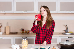 Girl with long flowing hair in a red men's shirt. kitchen cup his hands Royalty Free Stock Image