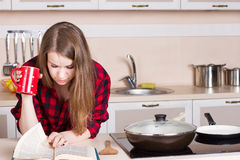 Girl long flowing hair a red men's shirt in the kitchen with cup his hands Royalty Free Stock Photography