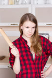 Girl long flowing hair red men's shirt with a rolling pin in the kitchen Royalty Free Stock Image
