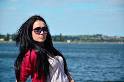 Girl with long flowing hair on sea background. Beautiful model with dark hair on sea background Stock Image
