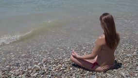 A girl with long flowing hair in a swimsuit sits on the beach in waves meditating in a lotus pose. 4K stock footage