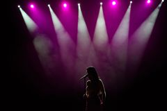 Girl in long gown performing on stage. Girl singing on the stage in front of the lights. Silhouette of singer standing. On stage at microphone royalty free stock image