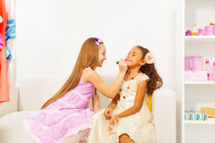 Girl with long hair applies lipstick on her friend Royalty Free Stock Photography