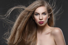 Girl with long hair. Beautiful young woman with natural makeup and blowing long blond healthy hair. Over dark grey background. Copy space Royalty Free Stock Photography