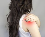 A girl with long hair clings to a sore shoulder medical royalty free stock photography
