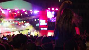 Girl with long hair at concert, bright flashes of color on stage, stage lighting and smoke, crowd jumping raising his stock footage