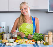 Girl with long hair cooking vegetables in kitchen. Happy girl with long hair cooking vegetables in kitchen Royalty Free Stock Photo