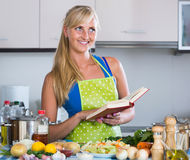 Girl with long hair cooking vegetables in kitchen. Pretty russian girl with long hair cooking vegetables in kitchen Royalty Free Stock Photos