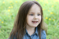 Girl with long hair among dandelion field Royalty Free Stock Photography